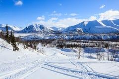 极性工业城市冬天视图包围与雪山 免版税库存照片