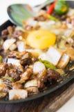 极热的猪肉sisig用未加工的鸡蛋 免版税库存照片