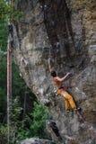 极端体育上升 在岩石墙壁上的年轻男性攀岩运动员 背景的斯诺伊森林 免版税库存图片