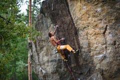 极端体育上升 在岩石墙壁上的年轻男性攀岩运动员 免版税图库摄影