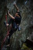 极端体育上升 在岩石墙壁上的年轻男性攀岩运动员 库存照片