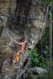 极端体育上升 在岩石墙壁上的年轻男性攀岩运动员 免版税库存图片