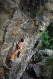 极端体育上升 峭壁的表面的攀岩运动员 免版税库存图片
