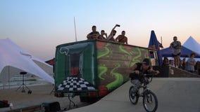 极端体育-自由式做在搬运车上的BMXer把戏在执行特技的比赛期间反对日落天空 影视素材