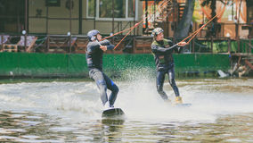 极端公园,基辅,乌克兰, 07可以2017年-乘坐Wakeboard的两三个年轻人,把戏和射击照相机 五谷p照片  图库摄影