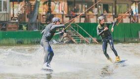 极端公园,基辅,乌克兰, 07可以2017年-乘坐Wakeboard的两三个年轻人,把戏和射击照相机 照片 库存照片