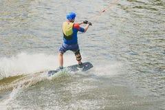 极端公园,基辅,乌克兰-可以, 07日2017年-一年轻人被实践的跳跃在Wakeboarding 处理五谷的照片 图库摄影