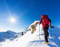 极端冬季体育:登山人在的多雪的山峰顶部 免版税库存照片