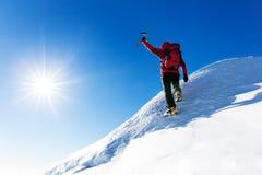 极端冬季体育:登山人在的多雪的山峰顶部 库存图片