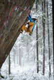 极端冬季体育 攀登与套住的年轻人一个岩石 绳索上升 库存图片
