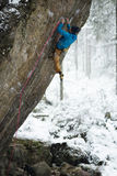 极端冬季体育 攀登与套住的年轻人一个岩石 绳索上升 图库摄影