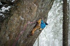 极端冬季体育 攀登与套住的年轻人一个岩石 绳索上升 库存照片