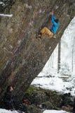 极端冬季体育 攀登与套住的年轻人一个岩石 绳索上升 免版税库存照片
