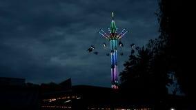 极端吸引力在游乐场,在一个行市看涨时买进的股票的吸引力转盘,多彩多姿与在黑暗的时间的电灯泡 股票录像