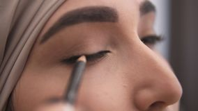 极端接近做箭头的观点的一名年轻回教妇女在她的眼皮使用黑eyepencil 震惊看  影视素材