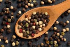 极端接近黑,红色,绿色和白色干胡椒的混合在一把木匙子的在黑色,土气石厨房板 库存图片