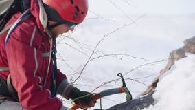 极端游人打破与空隙冰块夹子的耐久的雪 他佩带红色特别衣服、背包和保险 股票录像