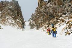 极端滑雪者在沿couloir的上面上升在岩石之间在backcountry的freeride的下降前 免版税库存照片
