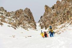 极端滑雪者在沿couloir的上面上升在岩石之间在backcountry的freeride的下降前 免版税库存图片