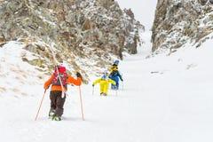 极端滑雪者在沿couloir的上面上升在岩石之间在backcountry的freeride的下降前 库存图片