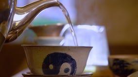 极端特写镜头视图男性手倾吐从水壶的面汤到从宜兴黏土woth手工制造凹道yin的gaiwan陶瓷碗 股票录像