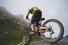极端登山车炫耀乘坐户外反对岩石背景的盔甲的运动员人  生活方式 试算 图库摄影