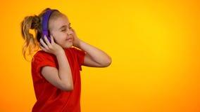 极端紫色耳机的滑稽的女孩听喜爱歌曲和跳舞的 免版税图库摄影