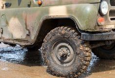 极端肮脏的SUV轮子在驾驶在雨中以后 库存照片