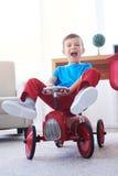 极端获得愉快的男孩乐趣,当乘坐在减速火箭的玩具汽车时 库存照片