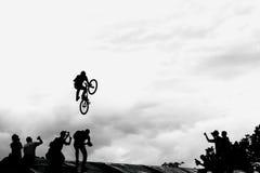 极端骑自行车者,做与bmx自行车的年轻人跃迁在黑白剪影和云彩背景  免版税库存照片