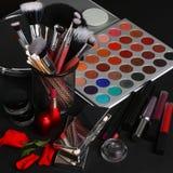 构成刷子和化妆用品在黑背景 免版税库存照片