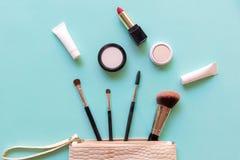 构成化妆用品工具和秀丽化妆用品、产品和面部化妆用品包裹唇膏,在绿色淡色背景的眼影 免版税库存图片