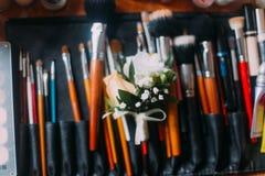 构成化妆用品的专家刷子与一朵逗人喜爱的小的钮扣眼上插的花 关闭 库存图片