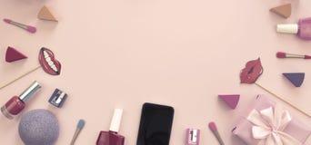 构成套装饰化妆用品指甲油唇膏海绵磨削器手机箱子礼物丝带缎弓背景pi 免版税库存图片