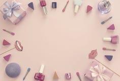 构成套装饰化妆用品指甲油唇膏海绵磨削器箱子礼物丝带缎弓背景桃红色 库存照片
