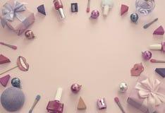 构成套装饰化妆用品指甲油唇膏海绵磨削器箱子礼物丝带缎弓背景桃红色 免版税库存照片