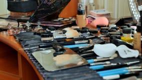 构成工作者` s书桌 许多化妆用品在桌上驱散 化妆师绘模型 免版税库存图片