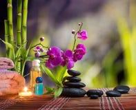 构成温泉按摩-竹子-兰花、毛巾、蜡烛和黑石头 库存图片