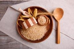 构成用在一个木棕色碗的未加工的米有一把木小铲和匙子的 顶视图 图库摄影