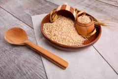 构成用在一个木棕色碗的未加工的米有一把木小铲和匙子的 免版税库存图片