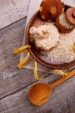 构成用在一个木棕色碗的未加工的米有一把木小铲和匙子的 库存照片