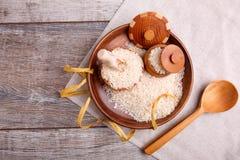 构成用在一个木棕色碗的未加工的米有一把木小铲和匙子的 免版税库存照片