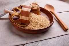 构成用在一个棕色碗的未加工的米有一把木小铲和匙子的 图库摄影