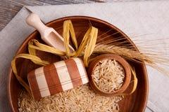构成用在一个棕色碗的未加工的米有一把木小铲和匙子的 黑色接近的耳机图象软绵绵地查出话筒填充白色 库存照片