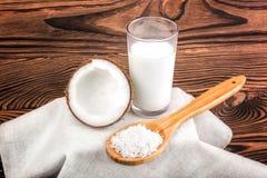 构成用在木背景的椰奶 切开椰子和一块玻璃有很多有机新鲜的牛奶和匙子有坚果芯片的 免版税库存照片