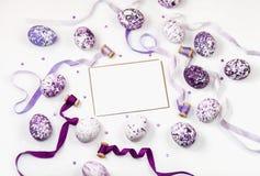 构成用紫罗兰色复活节彩蛋、衣服饰物之小金属片和丝绸丝带在白色背景 问候文本的空间 复活节 免版税库存照片