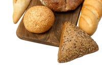 构成用面包和卷在白色隔绝的切板 免版税库存照片