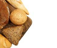 构成用面包和卷在白色隔绝的切板 免版税库存图片