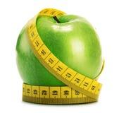 构成用绿色苹果和在白色的卷尺 免版税库存照片