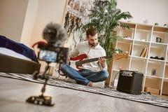 构成音乐次幂正方形 关闭有弹电吉他的男性音乐博客作者的数码相机屏幕和记录新 图库摄影